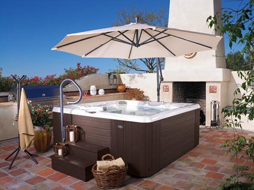 A scene of a beautiful patio with a hot tub in the center and a spa side umbrella overhead on a sunny day