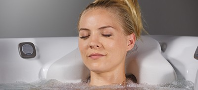 image of a woman enjoying a relaxing soak in a caldera spa