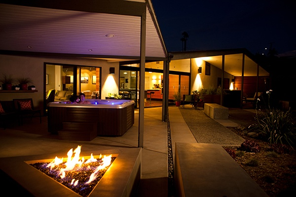 night scene of a couple relaxing in a beautifully designed back yard with a vacanza tarino hot tub